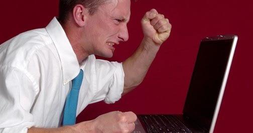 Angry guy making fist at computer