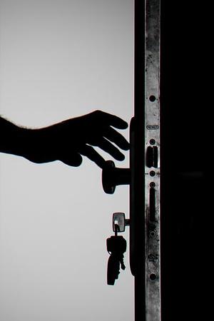 person-reaching-for-doorknob-with-keys-in-door