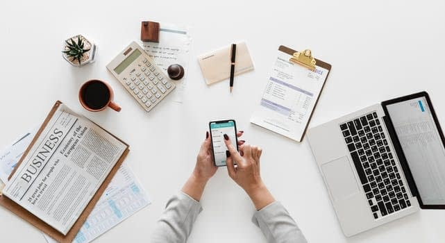 Computer, phone, calculator on a desk