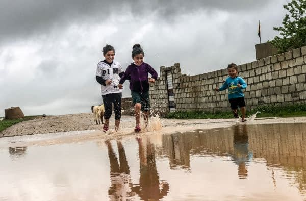 Kids smiling and jumping in puddles