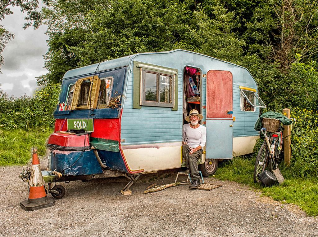 Man sitting in open camper door.