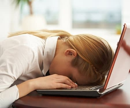 woman faceplanting in frustration in laptop computer