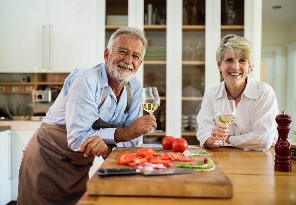 Elderly couple drinking wine at a kitchen island.