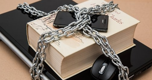 Computer and cell phone wrapped in chains