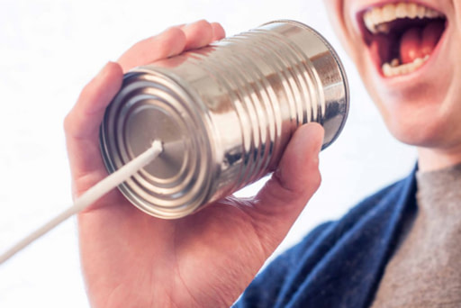 person talking into a tin can phone