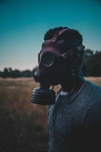 man in a gas mask in a field