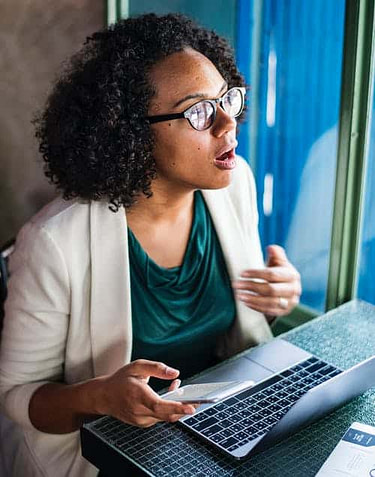 woman looking surprised at computer with cell phone in hand