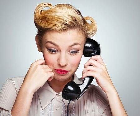 Retro woman talking on rotary phone.